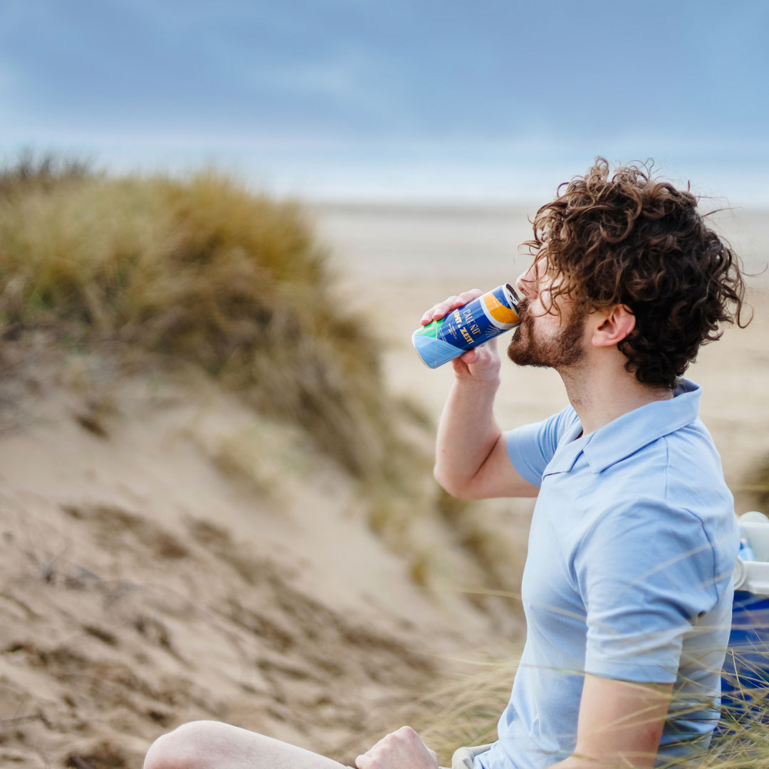 Man drinking Caleno Can on the beach