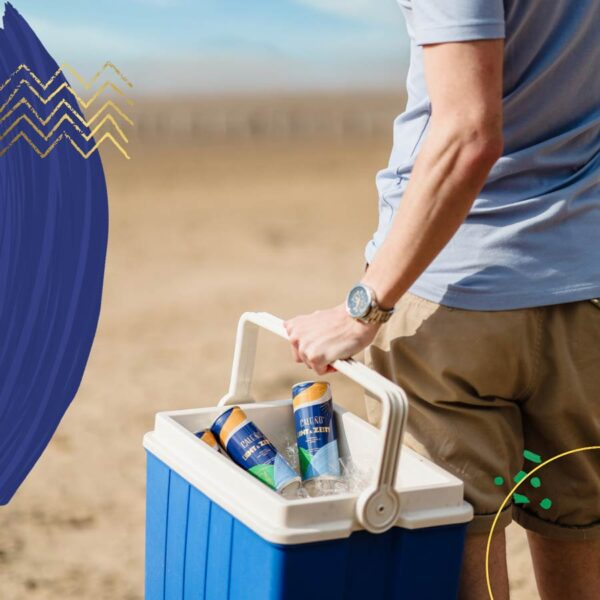 Man on beach with Caleno Light & Zesty cans in a coolbox